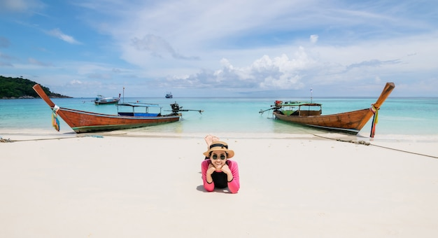 Women lie on the beach and the sea have a holiday summer relaxing Premium Photo