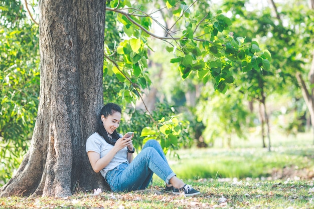 Women listen to music and relax under the trees. Premium Photo