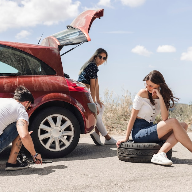 Women looking at a man changing the car wheel on the road Free Photo