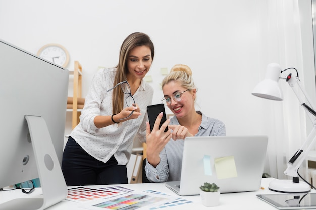 Women looking on phone at office Free Photo