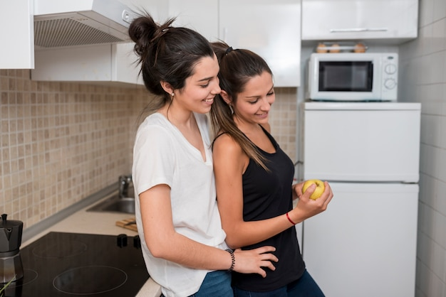 Women in love hugging in kitchen Free Photo
