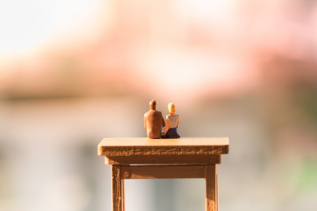 A women and a man in love sitting on ladder with light copy space. Premium Photo