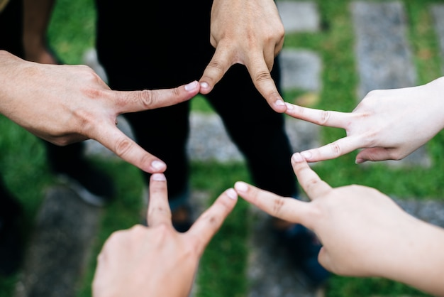 Women and men friends make star shape from fingers. success, friendship concept. Free Photo