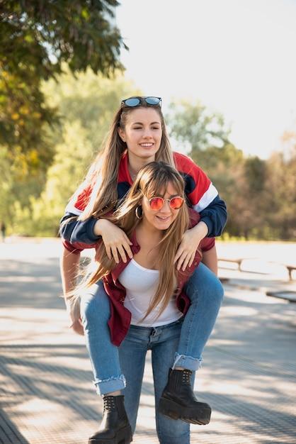 Women piggyback her girlfriend Free Photo