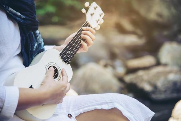 Women play ukulele new to the waterfall Free Photo