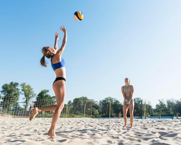 Donne che giocano insieme a pallavolo sulla spiaggia Foto Gratuite
