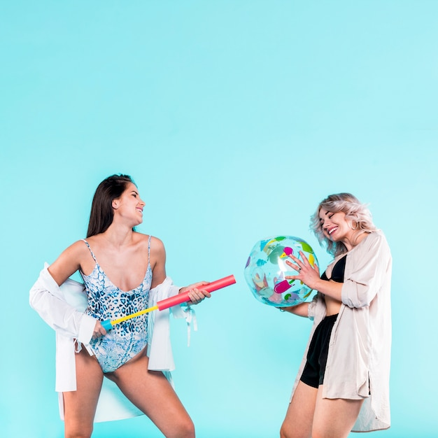 Women playing with beach ball and pump Free Photo
