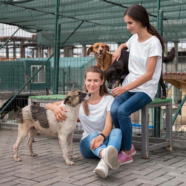 Donne che giocano con la cura cani da salvataggio al rifugio Foto Gratuite