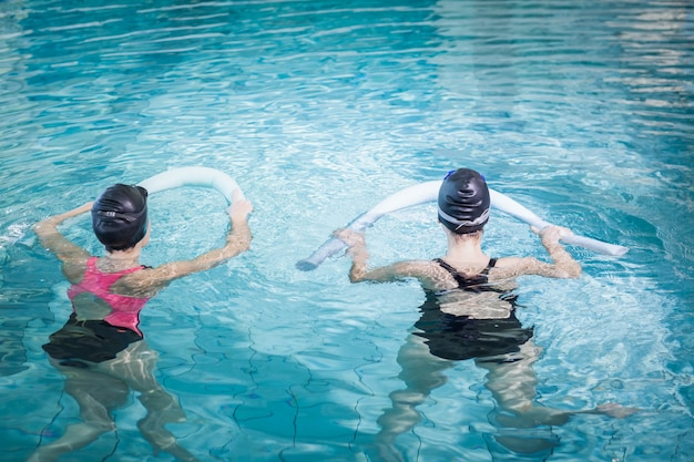 Women in the pool with foam rollers at the leisure center Premium Photo