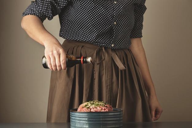 여성은 만두 또는 라비올리 요리를 위해 다진 고기에 간장 소스를 붓습니다. 무료 사진