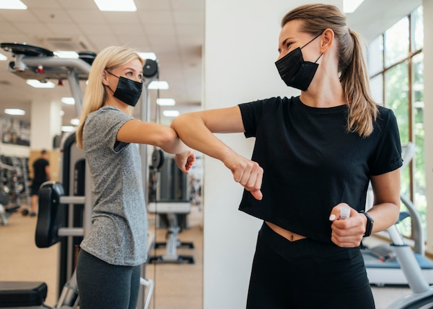Women practicing the elbow salute at the gym during the pandemic Free Photo