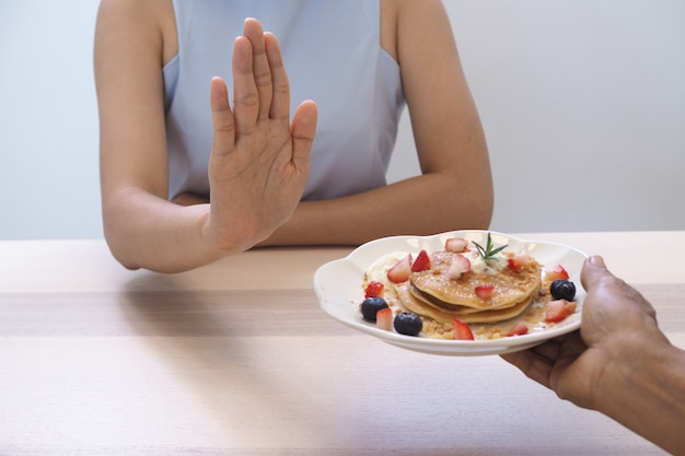 Women pushed pastry dishes. stop eating dessert, good health Premium Photo