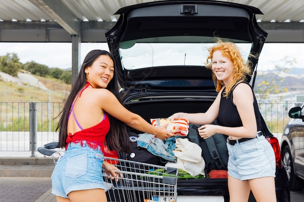 Women putting purchases in trunk of car in parking lot and looking at camera Free Photo