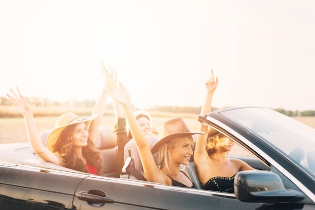 Women riding car with hands up Free Photo