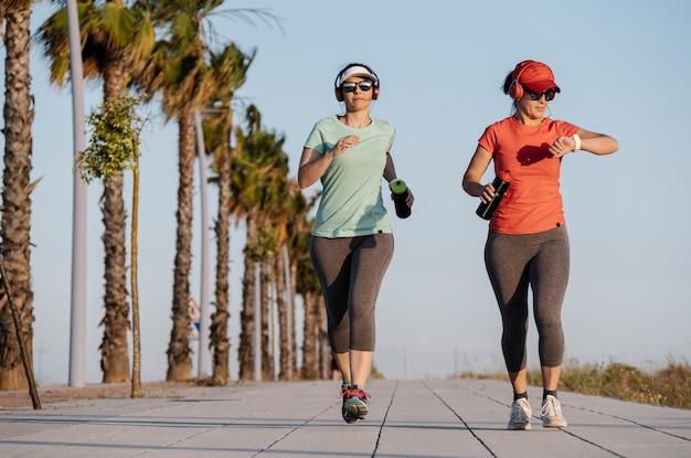 Женщины бегут по дороге и слушают музыку Premium Фотографии