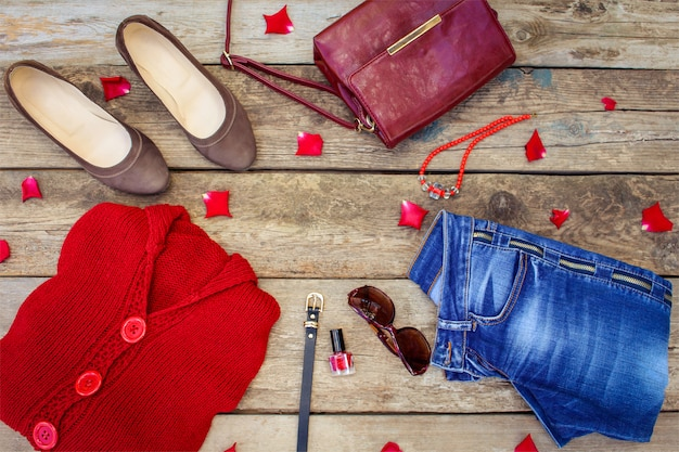 Women's autumn clothing and accessories: red sweater, jeans, handbag, beads, sunglasses, nail polish, shoes, belt on wooden . top view. Premium Photo