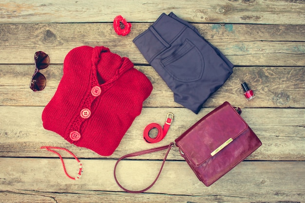Women's autumn clothing and accessories: red sweater, pants, handbag, beads, sunglasses, nail polish, hair band, belt on wooden background. toned image. Premium Photo