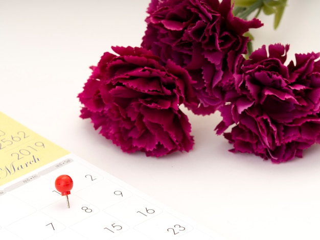 Women's day on calendar with red pin. Premium Photo