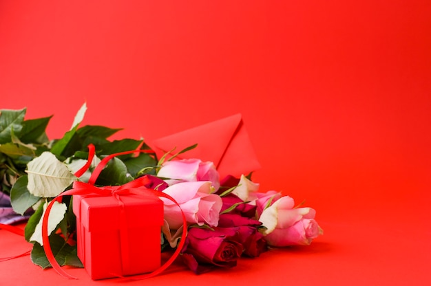 Women's day concept and valentine's day greeting card. composition with gift, roses and envelope. space for text. Premium Photo