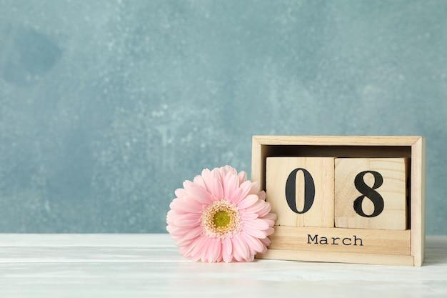女性の日3月8日、木製ブロックカレンダー。母の日おめでとう。白いテーブルの春の花。テキストのためのスペース Premium写真