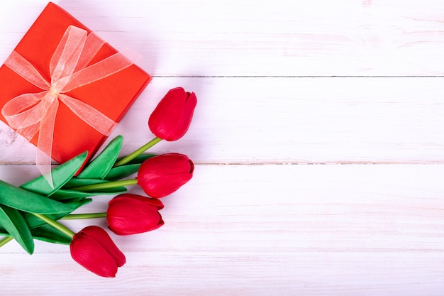 Women's day, mother's day, valentine's day concept red tulips bouquet and a gift Premium Photo