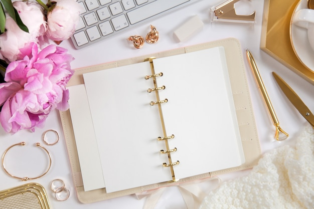 Women's diary and golden stationery. bouquet of pink peonies. glasses, a white keyboard, pen, scissors and coffee on the desktop. Premium Photo