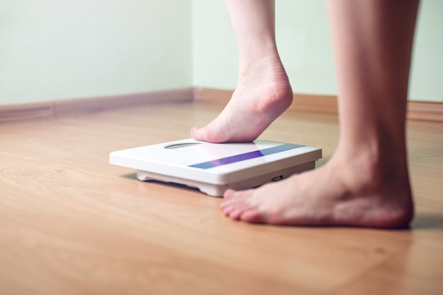Women's feet are on mechanical scales for weight control Premium Photo