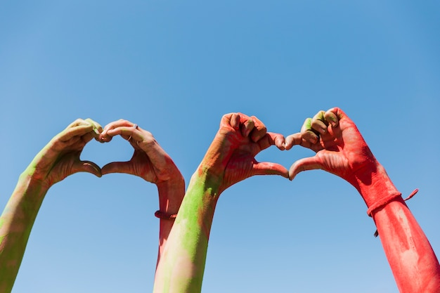 Women's hand showing heart shape against blue sky Free Photo