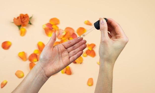 물방울과 장미 오일을 적용하는 여자의 손. 피부 관리 개념. 자연 의학. 프리미엄 사진