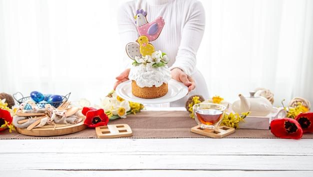 女性の手は、花と明るいディテールで飾られたお祝いのイースターケーキを持っています。イースター休暇の準備の概念。 無料写真