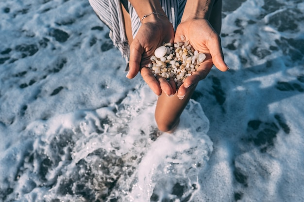 Women's hands are holding a lot of small pebbles Free Photo