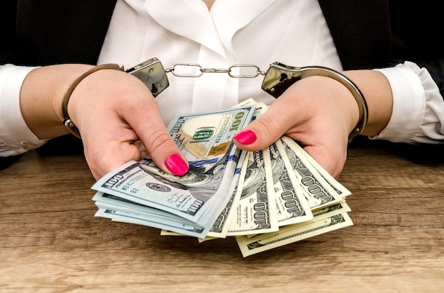 Women's hands in handcuffs with dollars in their hands Premium Photo