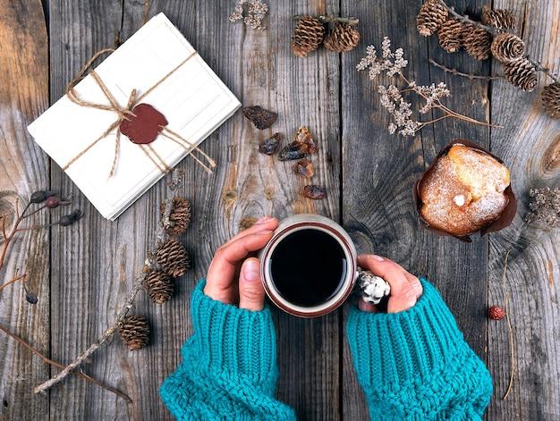 Женские руки держат керамическую кружку с черным кофе, серый деревянный стол Premium Фотографии
