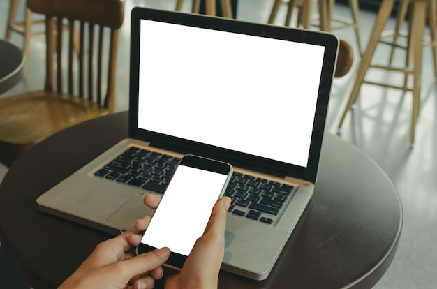 Women's hands holding mobile phone and computer laptop Premium Photo