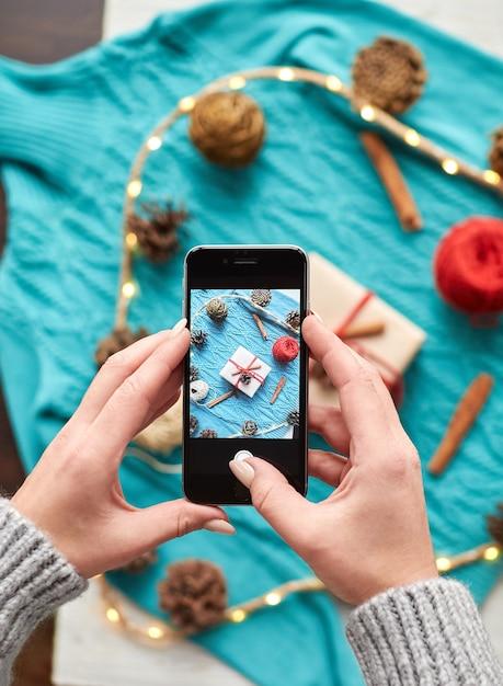 Женские руки снимают на смартфон новогоднюю композицию сверху. создавайте и упаковывайте рождество и подарки к празднику. подарки родным и близким с поздравлением Premium Фотографии