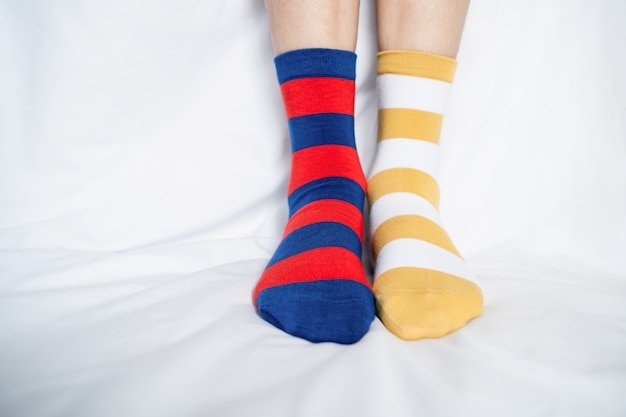 靴下色の女性の足が交互に、白い布の床の上にサイドスタンド。 Premium写真