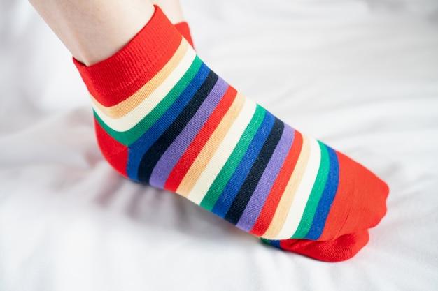 靴下で女性の足は、いくつかの色が交互に、白い布の床の上に横に立ちます。 Premium写真