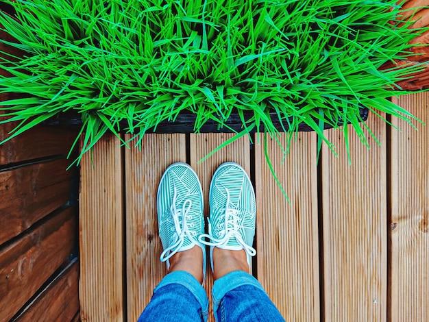 Women's legs in mint sneakers on terrace board with artificial grass in flowerpot Premium Photo