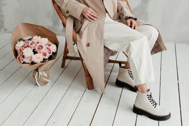 흰색 바탕에 여자의 다리입니다. 꽃 꽃다발과 소녀의 다리. 여자의 발에 장미 꽃다발. 프리미엄 사진