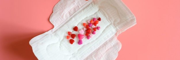 Women's menstrual sanitary pad or napkin for normal profusion of secretions with red and pink beads in the shape of hearts as an imitation of blood on pink background. Premium Photo