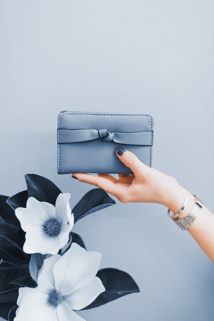 Women's stylish wallet in the hands of a girl with a dark blue manicure. the color of the year 2020. Premium Photo