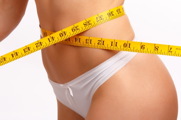 Women's waist with a tape measure Free Photo