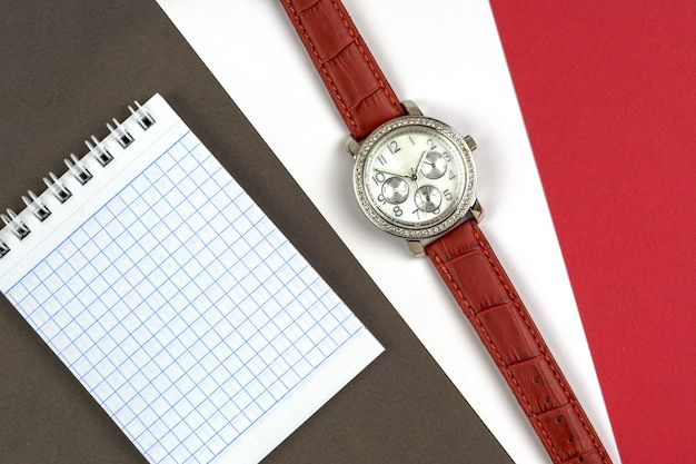 Women's watch and notebook on grey, white and red backgrounds Premium Photo