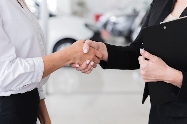 Women shaking hands in car show room Free Photo