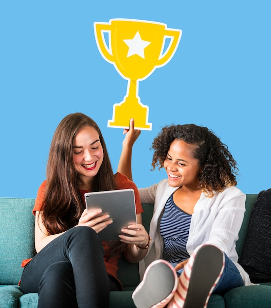 Women showing a trophy icon and using a tablet Free Photo