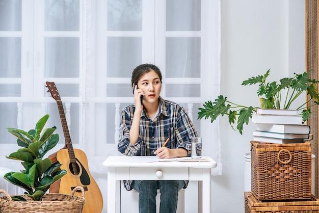 女性は机に座って電話を使って調整します。 無料写真