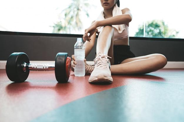 女性は運動後、座ってリラックスします。水筒とダンベルがあります。 無料写真