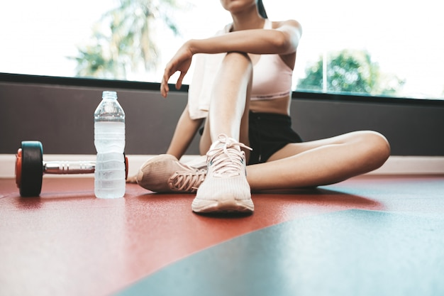 Women sit back and relax after exercise. there is a water bottle and dumbbells. Free Photo
