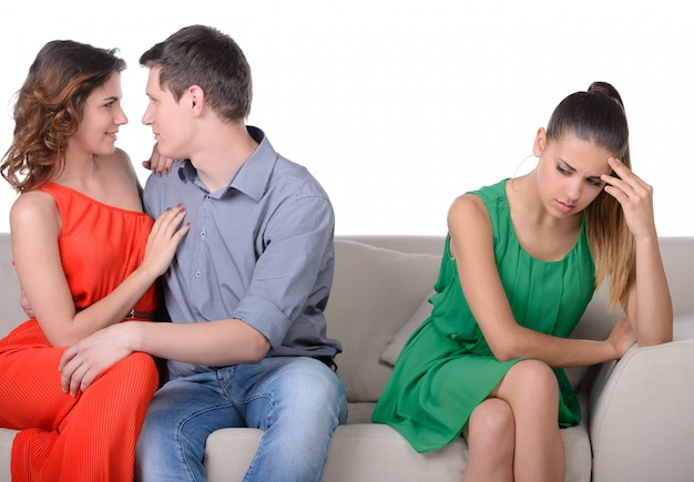 Women sitting on couch while another women with man. Premium Photo