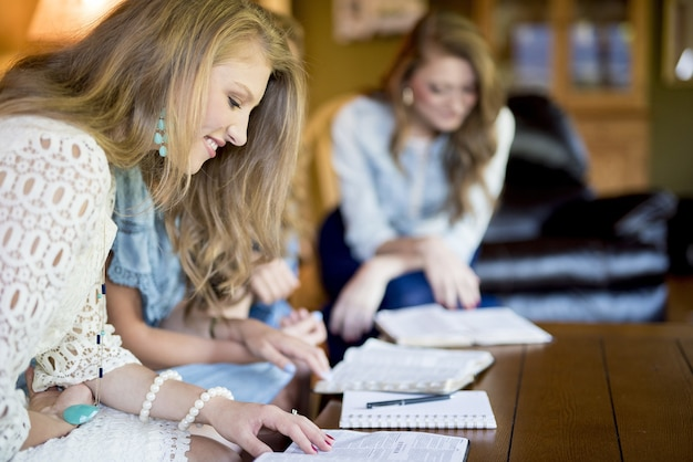 Donne sedute una accanto all'altra che studiano in una stanza Foto Gratuite